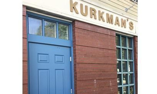 front of commercial building - brick with the word, Kurkman's on it, a blue door and a window