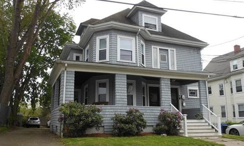 multi-family gray home shown - front of building with porch