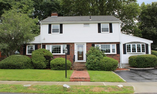 4 bedroom colonial sold in Belmont, MA - exterior of home shown, white with partial brick front