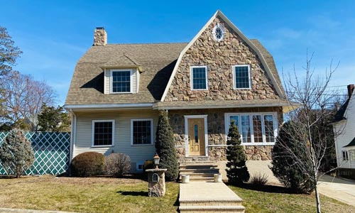 Dutch Colonial style home for sale in Watertown, MA - tan with white trim and lots of stone work on the front