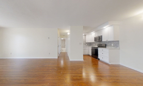 large empty room with hardwood flooring - view of a hallway and a modern gray and white kitchen with black and stainless steel appliances in the background