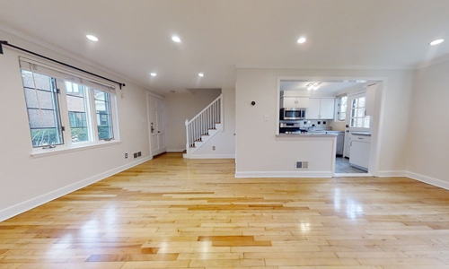 large empty room with hardwood floors, pale walls, three windows, an opening to a kitchen and a view of a staircase in the background