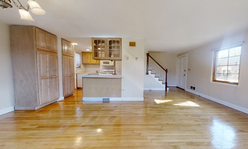 empty room with harwood floors, large built in gray cabinets, view of kitchen in the background on the left and entrance and stairs on the right