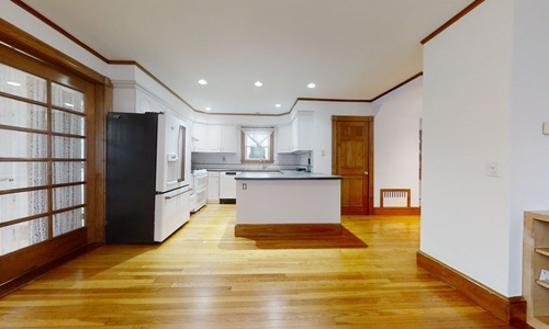 large empty room with hardwood flooring - view of a modern gray and white kitchen with black counters and white appliances in the background