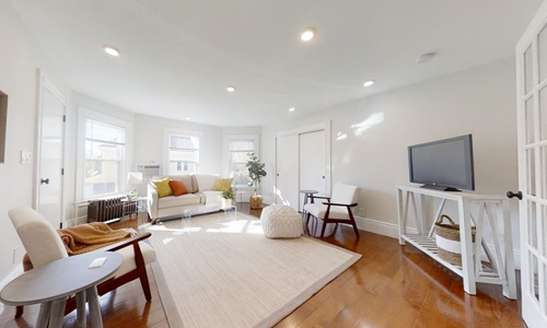 living room with harwood floors, light walls with white trim, white furniture with colorful pillows, three windows, recessed lighting and a french door