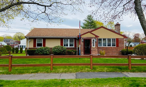 Three bedroom ranch for sale in Waltham, MA - exterior of home shown - tan with dark reddish brown trim and a partial brick front surrounded by a pretty front lawn that is fenced in.