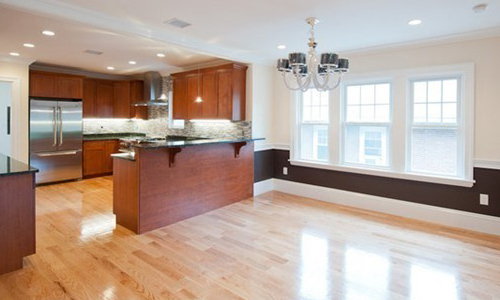open concept living area with kitchen in view; there are with lots of warm wood cabinets, stainless steel appliances, two-toned colored walls and hardwood floors
