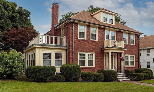 Stately brick colonial style home for sale in Belmont, MA - front exterior of home with closed in porch and second level deck to the left - the front entrance is covered and has pillars.