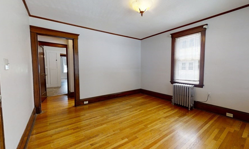 empty room with hardwood floors, white walls and wooden trim; a radiator sits below a window