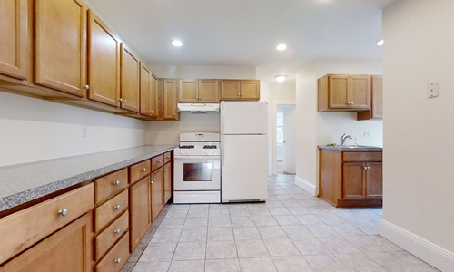 kitchen with lots of warm wood cabinets, white appliances, light walls and floor