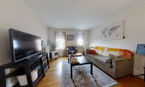 furnished living room with hard wood floors, light walls