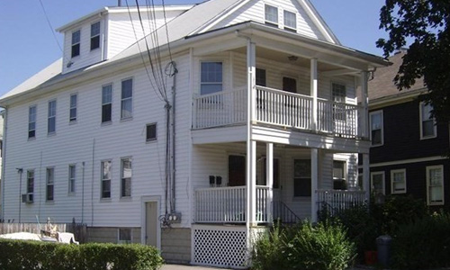 exterior of white multi family home with double porches out front