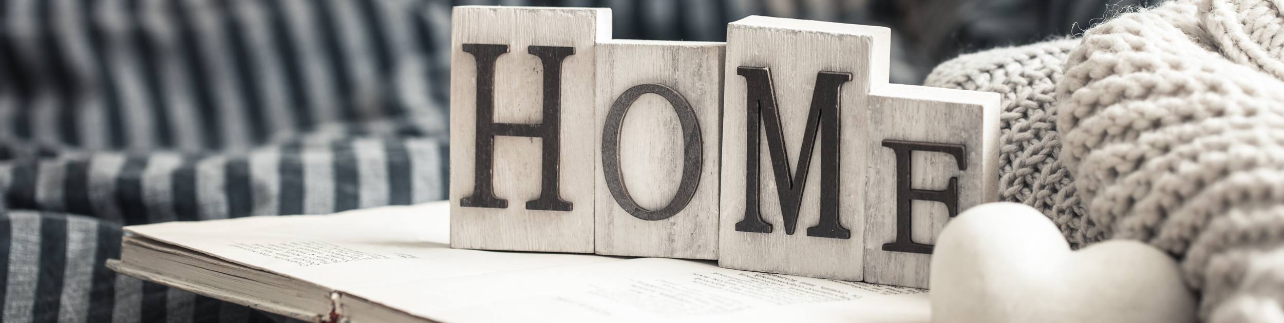 The word HOME spelled out in wooden blocks in a cozy environment