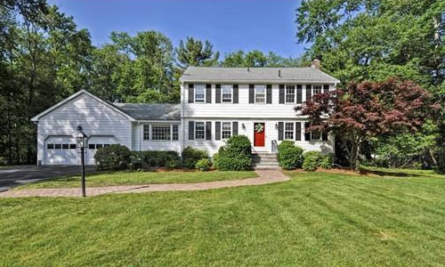 Detached White Colonial with red door, beautiful lawn surrounded by trees