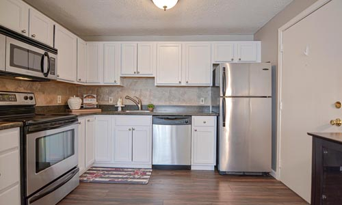 Two bedroom unit at Laurel Ridge Condominiums in Manchester, NH - view of beautifully renovated kitchen is shown with white cabinets and stainless steel appliances