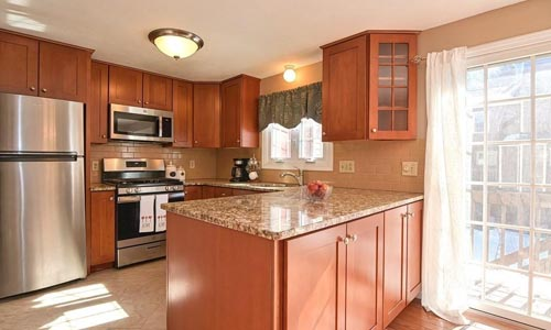 Two bedroom condo in Tewksbury, MA - view of kitchen is shown with new cabinets, granite counters and stainless steel appliances
