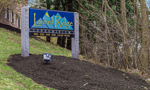 Laurel Ridge Condominiums sign on granite posts in a bark mulch bed