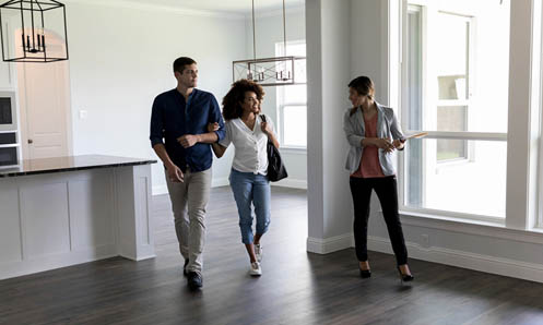 Real Estate Agent walking ahead of couple showing a new construction home
