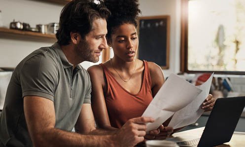 Man and woman looking at paperwork near computer
