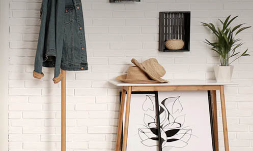 entrance hallway with denim jacket on coat rack, a small table with hats and a plant and a decorated white wall