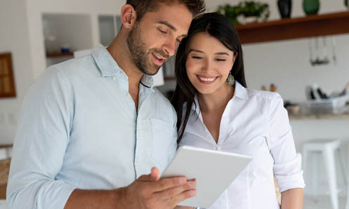 man and woman reviewing paperwork in kitchen