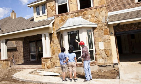 construction worker pointing up to a new home showing a man and woman something about the home