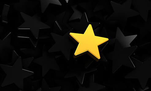 one gold star sitting on a pile of black stars