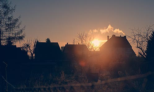 Multiple homes at dawn with the sun rising in the background.