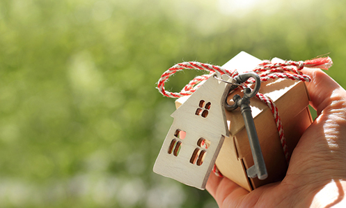 A hand holding a small box with a red and white rope holding a key and a small house on it.