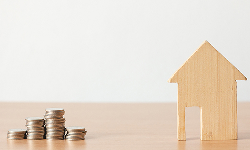 A wooden house with piles of coins near it.