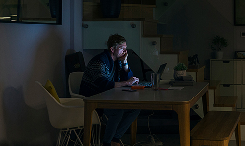 Man looking at a laptop screen at a table in a dimly lit room.