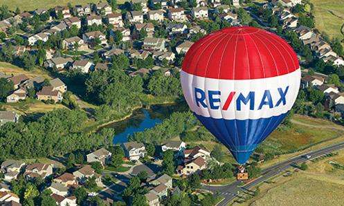 RE/MAX balloon flying over a neighborhood.