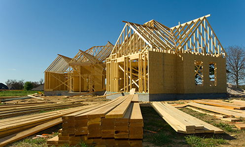A large home that is in the framing process of being newly constructed with lots of wood on the ground in front of it.