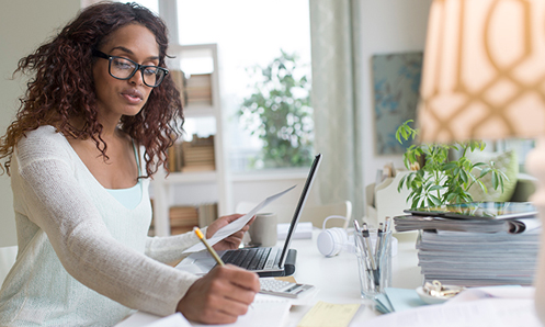 woman writing on notebook while holding more paper in her other hand sitting at a busy desk