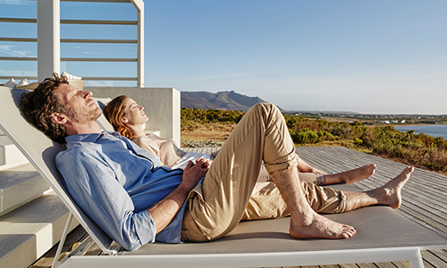 man and woman relaxing in the sun near a body of water