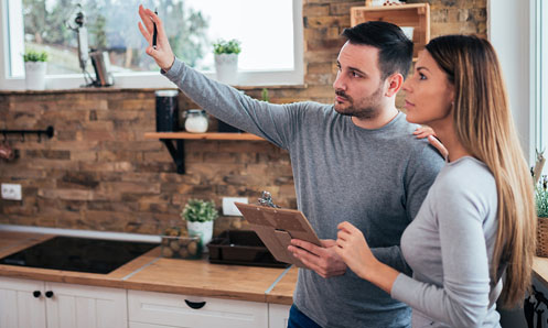 Man and woman in kitchen.  Man is holding clipboard and pointing towards his vision of change.