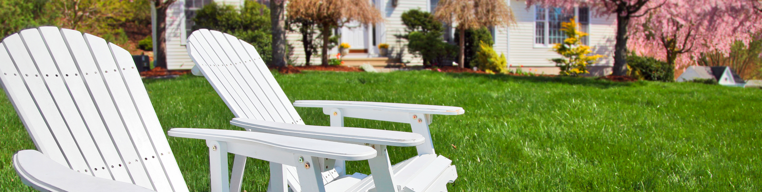 spring image - white house with blooming spring plantings out front and two white adirondack chairs sitting on a beautiful lawn