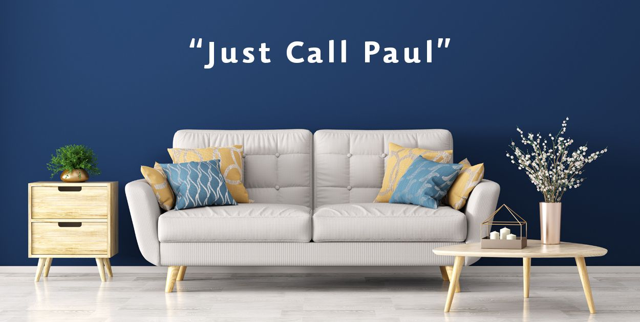 photo of couch with Just Call Paul written on a blue wall behind it