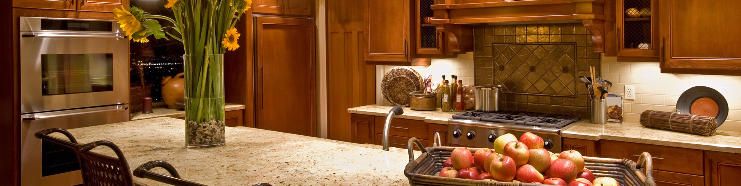 view of warmly colored kitchen with stainless steel appliances and granite counters - a large basket of apples and a vase of sunflowers are on the island