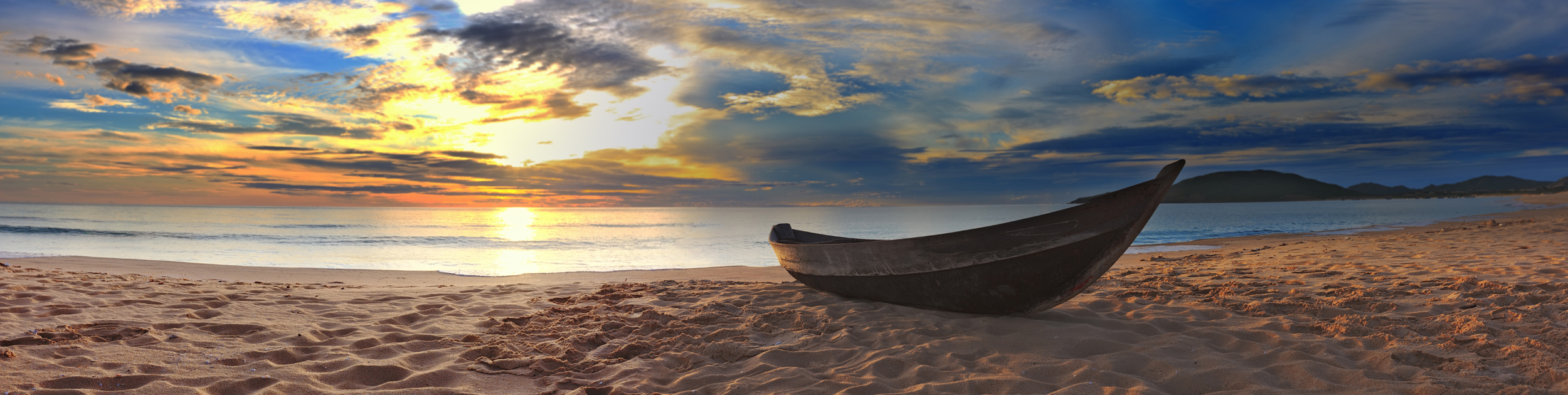 canoe resting on the shore of the ocean at sunset time