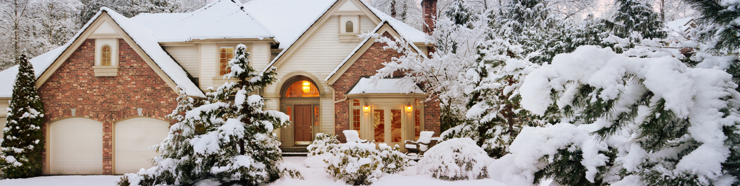exterior of brick front luxury home with snow covered landscaping