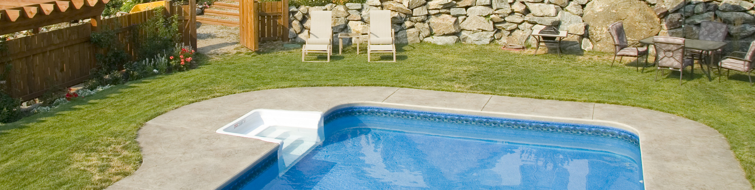 view of backyard with built in swimming pool, lawn furniture and stone wall