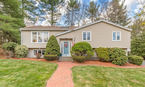 split entry style home - tan with white trim and blue door surrounded by trees and hedges with a brick walkway