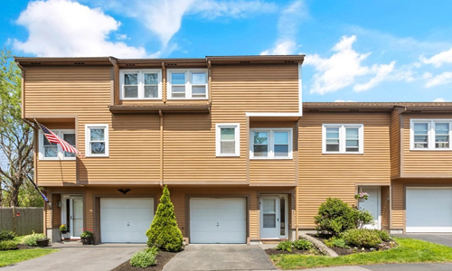 brown multi unit condo building with white trim, white doors and three driveways in view surrounded by blue sky