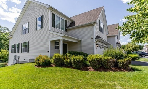 tan multi unit home with black shutters surrounded by trees and lots of shrubs out front.