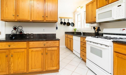 Condo for sale in Somerville, MA - kitchen shown with white appliances, black countertops and warm cabinets