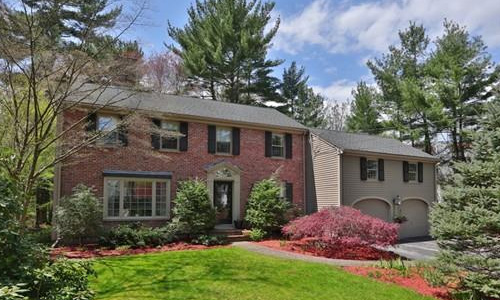 Detached Tan Colonial with brick front and 2 car garage