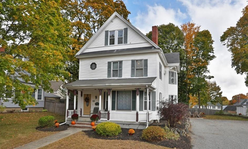 Detached White Colonial for sale - exterior of home shown - white with gray shutters, brick chimney and front porch.