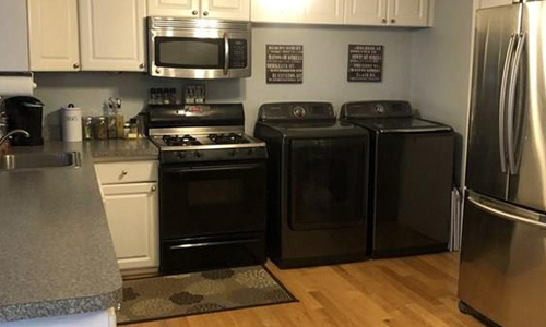 One bedroom apartment for rent in Boston, MA - black, white and stainless kitchen shown with hardwood floor, dark counters and ceiling fan light