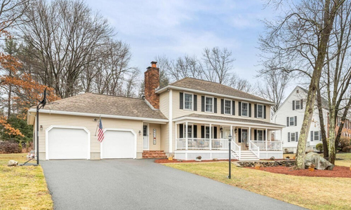 cream colored colonial style home with detached 2 car garage - home has a farmer's porch, black shutters and an American flag out front